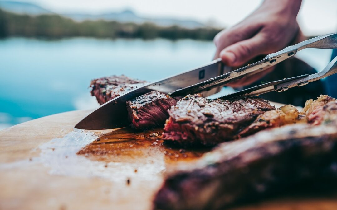 Cutting through steak on a wooden plank, cooked on KUDU grill